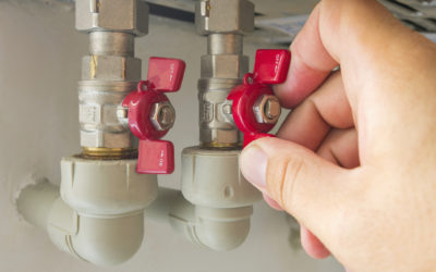 The man opens or closes the hot water valve in the boiler room at home, autonomous heating system.